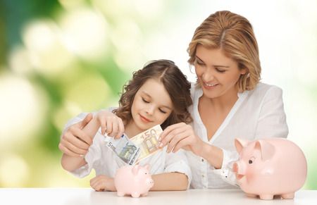 people, finances, family budget and savings concept - happy mother and daughter with piggy banks and paper money over green background