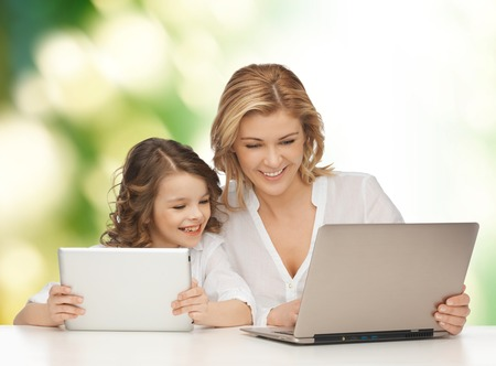 people, technology, family and parenthood concept - happy mother and daughter with laptop and tablet pc computers sitting at table over green background photo