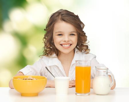 niños desayunando: alimentos saludables, comer, la gente y los niños concepto - feliz sonriente hermosa muchacha con desayuno sobre fondo verde Foto de archivo
