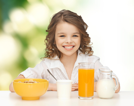 pre teen girl: healthy food, eating, people and children concept - happy smiling beautiful girl having breakfast over green background