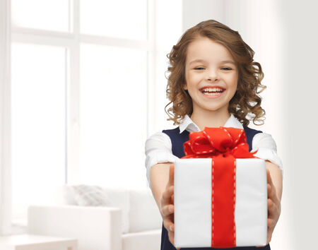 congratulating: people, childhood, summer and holidays concept - happy smiling girl with gift box over white room background Stock Photo