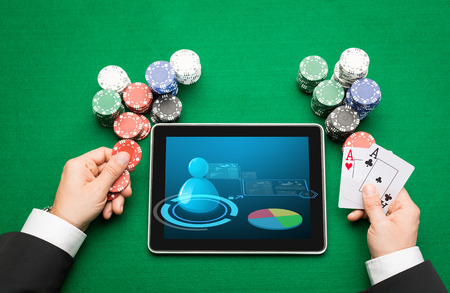 hold em: casino, online gambling, technology and people concept - close up of poker player with playing cards, tablet pc computer and chips at green casino table Stock Photo