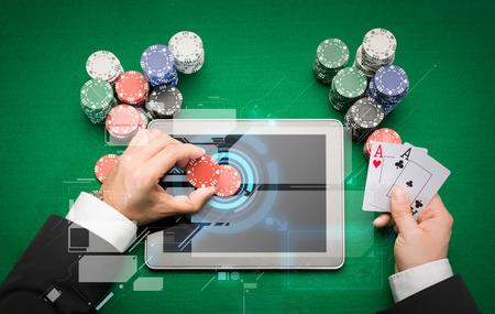 cartas de poker: casino, juegos de azar en l�nea, la tecnolog�a y el concepto de la gente - cerca de jugador de p�quer con naipes, tablet pc computadora y chips en la mesa de casino verde Foto de archivo