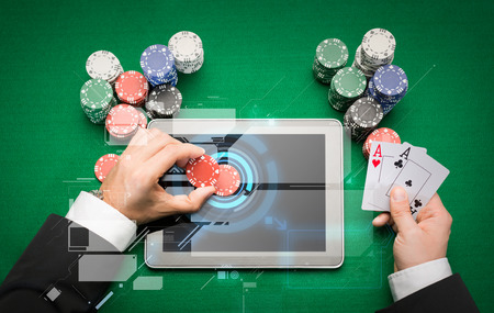 casino: casino, online gambling, technology and people concept - close up of poker player with playing cards, tablet pc computer and chips at green casino table Stock Photo
