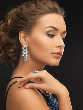 ear rings: woman in evening dress wearing diamond earrings and ring Stock Photo
