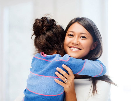 two women hugging: family, children and happy people concept - hugging mother and daughter Stock Photo