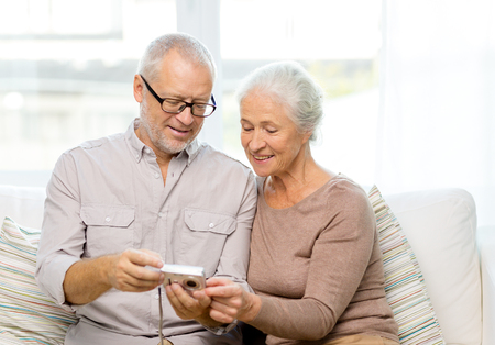 living together: family, technology, age and people concept - happy senior couple with camera at home