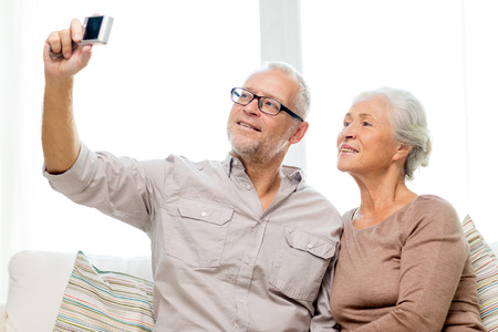 old sofa: family, technology, age and people concept - happy senior couple taking selfie with camera at home Stock Photo