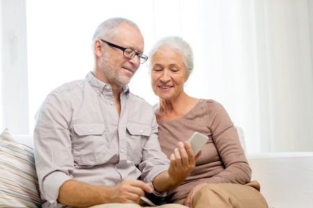 가족, 기술, 나이, 사람들이 개념 - 집에서 스마트 폰과 행복 수석 부부