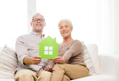 vejez feliz: la familia, las relaciones, los bienes raíces, la edad y el concepto de la gente - la feliz pareja senior con casa verde recorte de papel en casa
