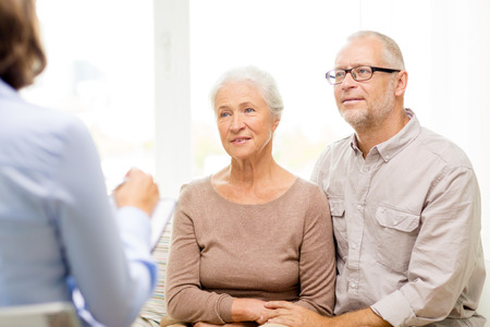 taking a wife: family, relations, age and people concept - happy senior couple and psychologist or social worker at home