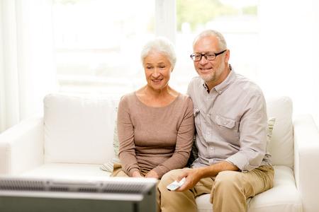 pareja viendo television: familia, la tecnología, la edad y el concepto de la gente - la feliz pareja senior viendo la televisión en casa Foto de archivo