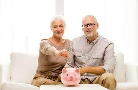 vejez feliz: familia, el ahorro, la edad y el concepto de la gente - sonriente pareja senior con dinero y una hucha en casa