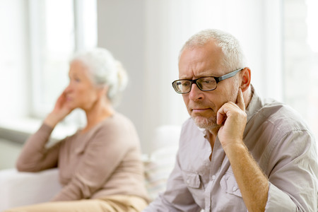 sad old woman: family, relations, age and people concept - senior couple sitting on sofa at home