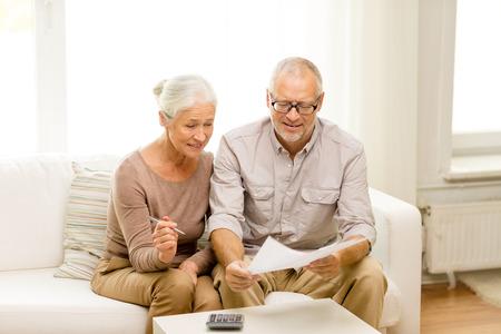 personas sentadas: familia, los negocios, el ahorro, la edad y el concepto de la gente - sonriente pareja senior con documentos y calculadora en casa