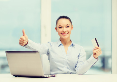 businesswoman card: business, investing and technology concept - businesswoman with laptop and credit card in office showing thumbs up