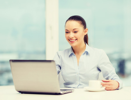 hot secretary: office, business and technology concept - smiling businesswoman or student with laptop computer and coffee in office