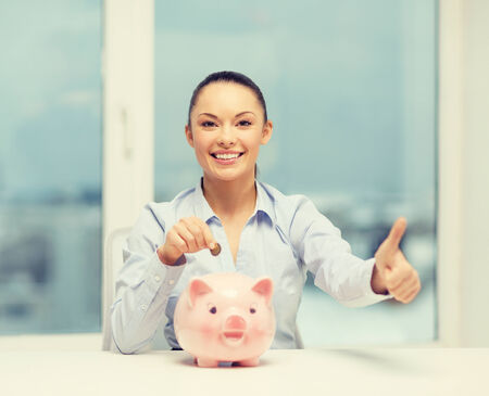 thrifty: banking and finances concept - lovely woman with piggy bank and cash money showing thumbs up