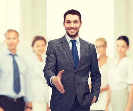 vítejte: obchodní a kancelářské koncepce - pohledný podnikatel s otevřenou dlaní připraven pro handshake