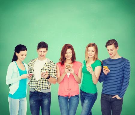 onderwijs en moderne technologie concept - lachende studenten met smartphones