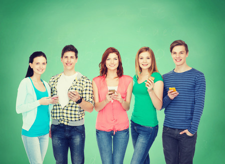 university application: education and modern technology concept - smiling students with smartphones Stock Photo