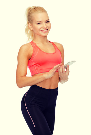 sport, fitness, technology, internet and healthcare - smiling sporty woman with smartphone Archivio Fotografico