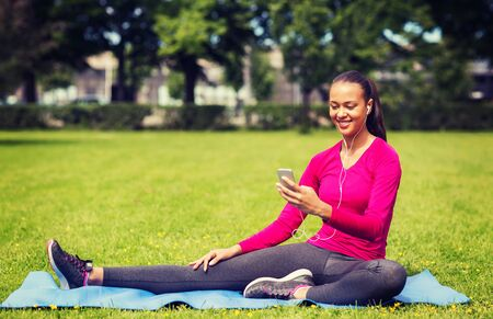fitness, park, technology and sport concept - smiling african american woman with smartphone and earphones sitting on mat outdoors
