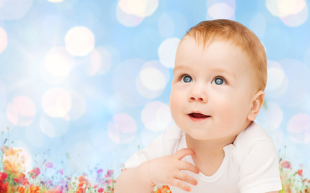 infancy: children, people, infancy and age concept - beautiful happy baby over blue lights and poppy field background Stock Photo