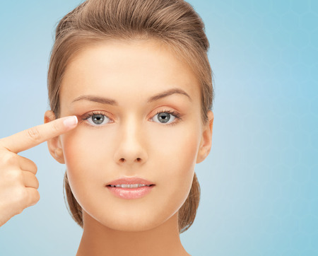beauty, people and health concept - beautiful young woman pointing finger to her eye over blue background Banque d'images