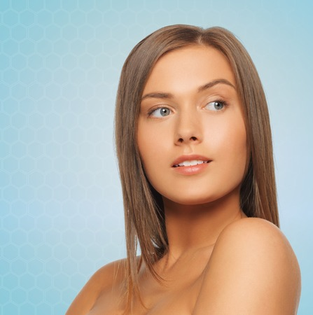 bare women: beauty, people and health concept - beautiful young woman with bare shoulders over blue background