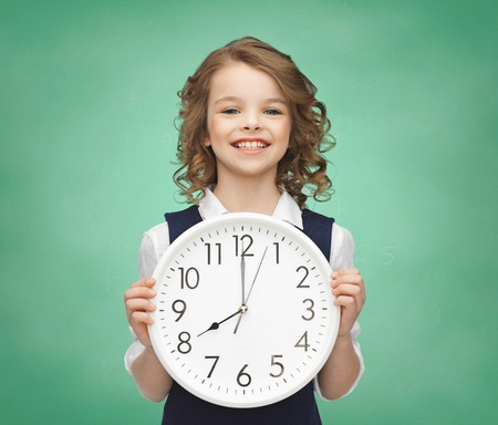 timezone: people, time management and children concept - smiling girl holding big clock showing 8 oclock