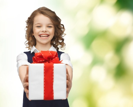 people, childhood, summer and holidays concept - happy smiling girl with gift box over green background Stockfoto