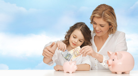 mother and teen daughter: people, finances, family budget and savings concept - happy mother and daughter with piggy banks and paper money over blue sky background