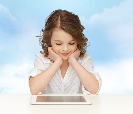 people, technology, education and children concept - happy smiling girl with tablet pc computer over blue sky background photo