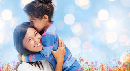 people, happiness, love, family and motherhood concept - happy mother and daughter hugging over blue lights and poppy field background photo