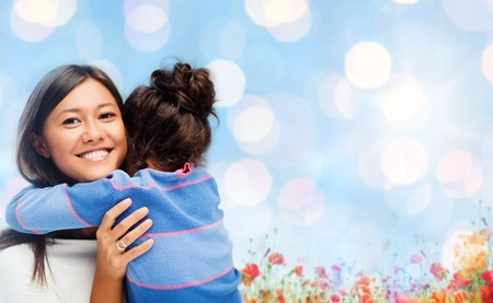 people, happiness, love, family and motherhood concept - happy mother and daughter hugging over blue lights and poppy field background Stock Photo