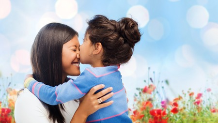 family, children and happy people concept - happy little girl hugging and kissing her mother over blue sky with lights and poppy field background