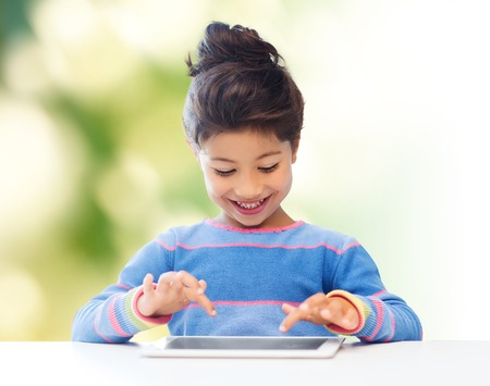 preteen asian: education, children, technology and people concept - happy little girl with tablet pc computer over green background Stock Photo