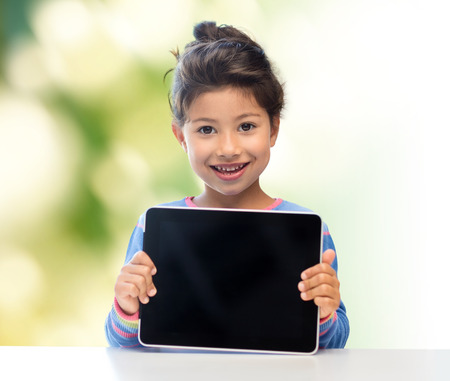 education, children, technology, advertisement and people concept - happy little girl with tablet pc computer over green background