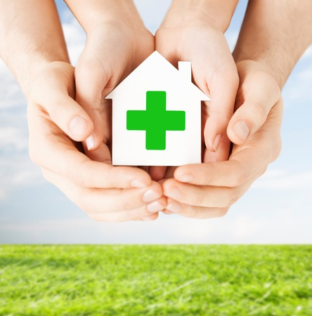 green cross: care, help, charity and people concept - close up of hands holding white paper house with green cross sign over blue sky and grass background Stock Photo
