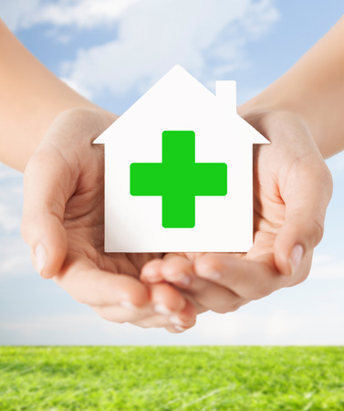eradication: care, help, charity and people concept - close up of hands holding white paper house with green cross sign over blue sky and grass background Stock Photo