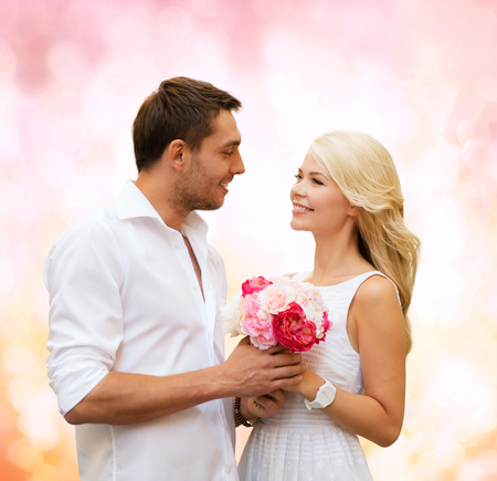 holidays, love, people and dating concept - happy couple with bunch of flowers over pink lights background photo
