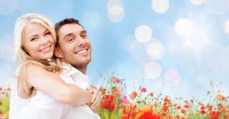 summer holidays, vacation, dating, love and people concept - happy couple having fun over poppy flowers field and blue sky background photo