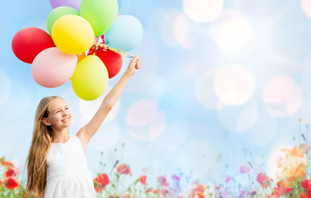 夏季休日、お祝い、子供および人々 コンセプト - 青色のライトやケシ畑の背景にカラフルな風船で幸せな女の子