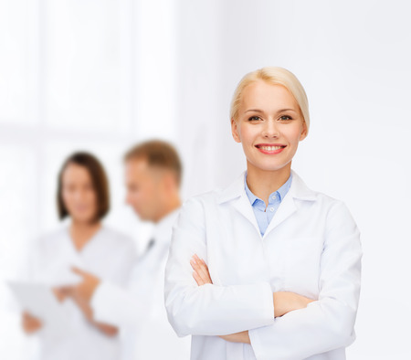 doctors smiling: healthcare and medicine concept - smiling female doctor over group of medics in hospital Stock Photo