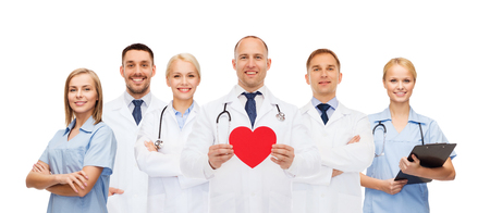 healthcare team: medicine, profession, teamwork and healthcare concept - group of smiling medics or doctors holding red paper heart shape, clipboard and stethoscopes over white background Stock Photo