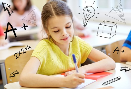 education, elementary school, learning and people concept - group of school kids with notebooks writing test in classroom over doodles Imagens