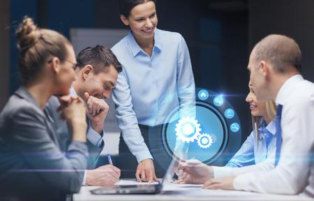 gestion empresarial: negocios, tecnología, fecha límite, la gestión y la gente concepto - sonriendo jefa hablar con equipo de negocios en la oficina la noche Foto de archivo