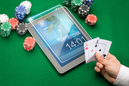 casino, online gambling, technology and people concept - close up of poker player with playing cards, tablet pc computer and chips at green casino table photo
