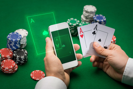 cards poker: casino, online gambling, technology and people concept - close up of poker player with playing cards, smartphone and chips at green casino table